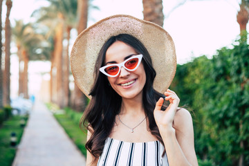 Following the journey. Affectionate girl with hazel-brown hair is smiling in front of green plants and planch path wearing taupe hat, white sunglasses with red glass and cotton biballs.