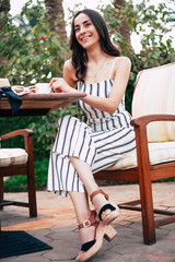 On the cloud nine. Bodacious woman is sitting on the overstuffed chair by the wooden table with a cup of tea wearing nice fitting jumpsuit and matching shoes.