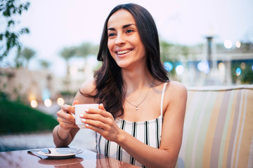 Flamboyant dream. Rejoicing girl in perfectly fitting jumpsuit combined from two colors with a cup of tea in her tiny hands in front of unfocused yellow and blue lights is smiling with a great joy.