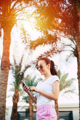 Under the sheen. A photo of a girl staying in the center of diversity of palm trees and yellow sun lights. She is wearing white and rose outfit with sunglasses  while using her phone.