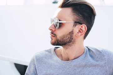 Presence over perfection. Admirable man with a beard on his face and nice hairstyle in front of bright white background wearing sunglasses with reflecting glass.