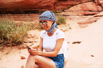 Splendid girl sitting among the green bushes, sand and rocks in white t-shirt, denim shorts, kerchief, a backpack and sunglasses. She is holding her phone and reacting happily to something.
