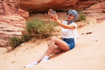 Memory of vocation. Sporty girl in summer outfit, perfect for hot climate, with a smartphone in her hands on which she is making memorable photos from the perfect holidays.