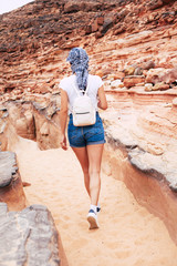 Follow me! A girl walking along the brownish rocks. She is dressed in leather sneakers, denim shorts, white t-shirt, three color kerchief  and she has a backpack over her shoulders.