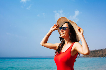 Bird of paradise. Fabulous girl is taking kisses from the sun on the blue shore of the sea clothed in red swimsuit and camel colored hat