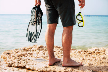 Explorer of underwater. A photo of the bottom part of men's body on a rock in black jockeys and swim fins with snorkel in his hand.