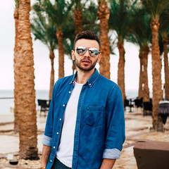 Man in denim shirt and sunglasses with a reflection of his fiancée is posing in front of dark green palms and terrace of the hotel.