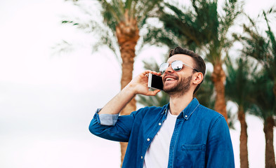 Gorgeous man among the green palm trees and light clear sky is talking by his smartphone and having joyful emotions.