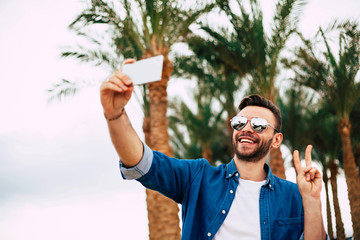 Have a nice day! Man with white smile is making a selfie in front of vibrant green palm trees and calm sky and sending happiness to all his friends.