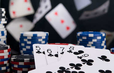 on a black background, flying cards for gambling, close-up, a set to win and a stack of chips to bet in the casino