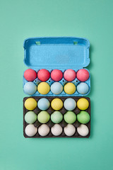 Multi-colored bright Easter eggs in a blue and black cardboard box on a green background with copy space. Easter layout for your ideas. Flat lay