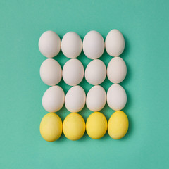 Pattern in the form of a square of painted yellow and white eggs on a green background with copy space. Billiard game concept. Flat lay