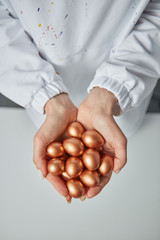 Golden painted small eggs hold the hands of a woman on a gray background. Concept of profit and wealth. Top view