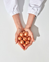 Closeup a lot of golden painted little eggs the girl's hands are holding on gray background with copy space. Wealth concept. Top view