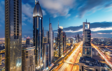 Aerial view on downtown Dubai, UAE with highways and skyscrapers. Scenic nighttime skyline. Wall mural
