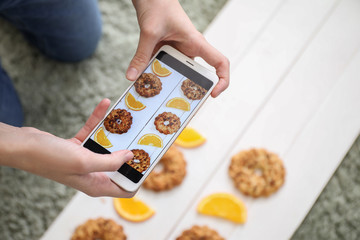 Female food photographer with mobile phone taking picture of tasty cookies and orange slices at home, closeup