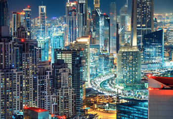 Fantastic rooftop view of a big modern city at night with illuminated skyscrapers. Architecture of the Business bay, Dubai, United Arab Emirates.