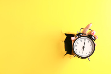 Female hand with alarm clock visible through hole in torn color paper Wall mural