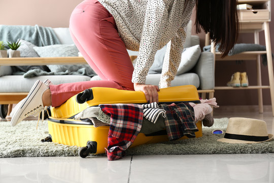 Woman trying to close suitcase with a lot of things. Travel concept