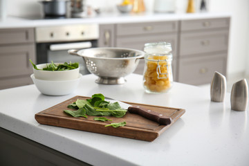 Fresh herbs with cutting board on table in kitchen