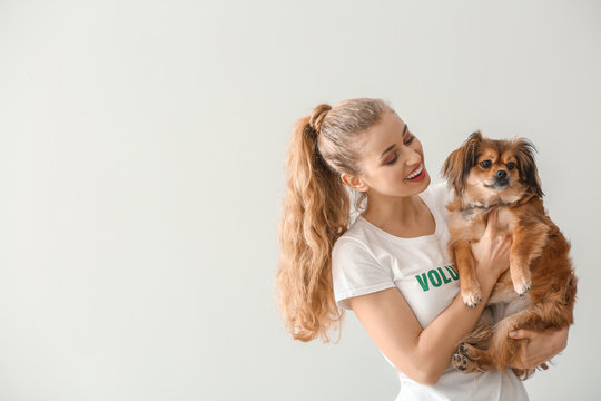 Young female volunteer with dog on light background