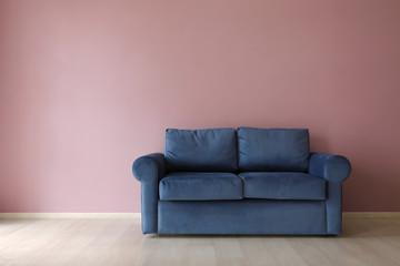 Comfortable sofa near color wall