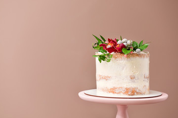 Sweet cake with floral decor on color background