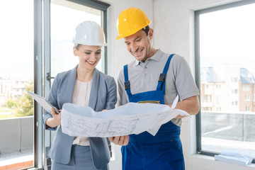 Construction worker and architect looking at plan on site