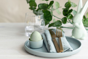 Happy Easter concept. Close up of Easter  Egg in mint green plate with  napkin. Scandinavian style  background with copy space .