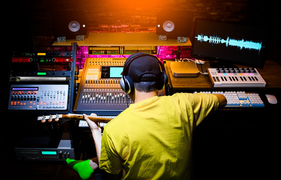 back of male asian musician recording guitar sound in home studio. music production concept