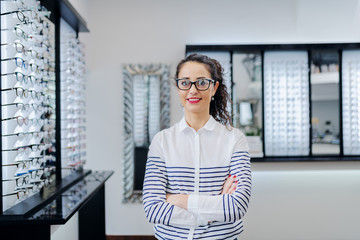Fototapeta Portrait of attractive Caucasian brunette with eyeglasses standing with arms crossed at ophthalmologist store.