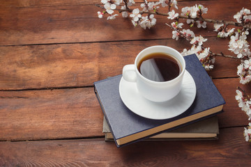 Sakura branches with flowers, White cup with Black Coffee and two books on a dark wooden background. Concept of Spring