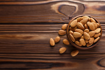 Delicious almonds in a wooden bowl on a wooden table, view from above