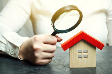 A woman is holding a magnifying glass over a wooden house. Real estate appraiser. Assessment of the condition of the house. Property valuation / appraisal. Search for housing and apartments.