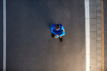 Top view of runner standing and watching at wristwatch. Healthy lifestyle concept.