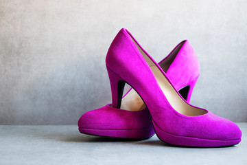 Bright pink high-heeled shoes on gray background.