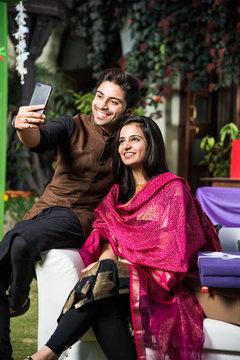 Smart indian couple taking selfie with smartphone on diwali or wedding party while sitting on sofa/couch