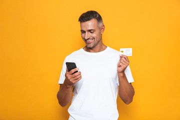 Image of beautiful guy 30s in white t-shirt holding mobile phone and credit card