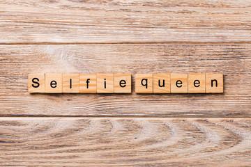 Selfie Queen word written on wood block. Selfie Queen text on wooden table for your desing, concept