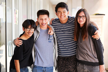 Portrait Of Smiling Male College Student Friends In Corridor Of Building