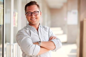 Portrait Of Smiling Male School Teacher Standing In Corridor Of College Building Wall mural