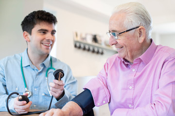 Male Doctor Measuring Blood Pressure Of Senior Man At Home