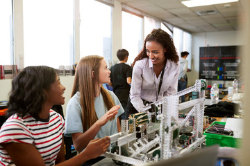 Woman Teacher With Female College Students Building Machine In Science Robotics Or Engineering Class