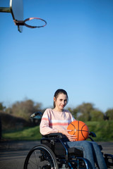 Portrait Of Teenage Girl In Wheelchair Playing Basketball