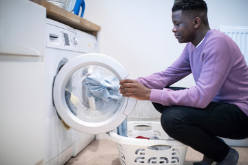 Teenage Boy Helping With Domestic Chores At Home Emptying Washing Machine