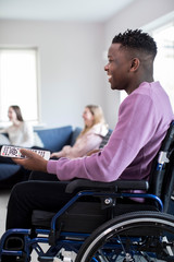 Teenage Boy In Wheelchair Watching Television With Freinds At Home