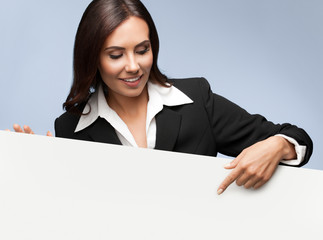 businesswoman showing blank signboard on grey