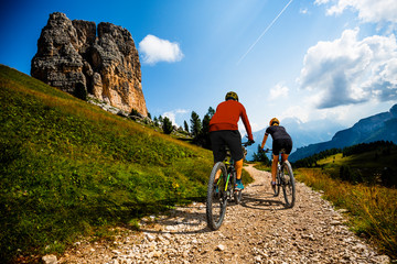 Cycling woman and man riding on bikes in Dolomites mountains landscape. Couple cycling MTB enduro trail track. Outdoor sport activity. Fototapete