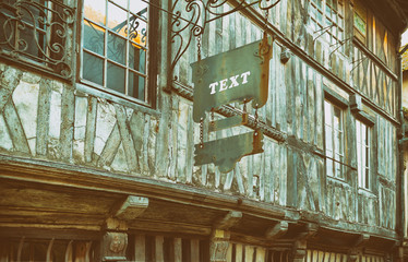 Ads text. Hanging sign advertising panel on facade of an old European wooden building.