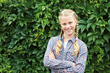 A teenage girl is smiling in the summer garden against a background of a wall of green leaves. Portrait